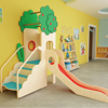 Small indoor playground with wooden slide
